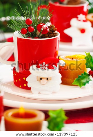 Photo of New Year eve table setting, closeup Christmas still life, Christmastime decoration for dinner, red and white festive utensil with candle and Santa Claus decoration, wintertime holiday