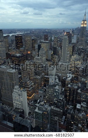 Photo of New York city as it's becomes nighttime. Empire State Building to the right. - stock photo