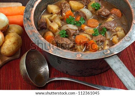 Photo of of Irish Stew or Guinness Stew made in an old well worn copper pot. - stock photo