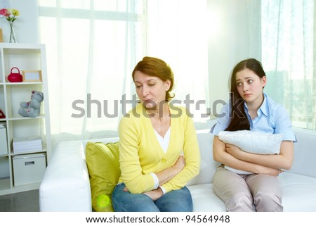Photo of offended woman sitting on sofa with her teenage daughter being sorry for what she did - stock photo