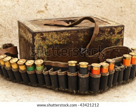 Photo of old ammunition belt with shells and vintage rusty chest against beige background - stock photo