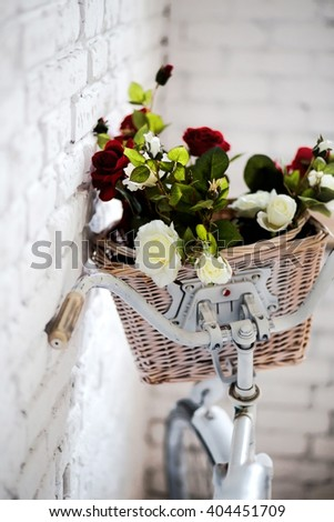photo of Old bicycle and flowers close to the white brick wall - stock photo