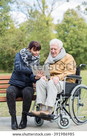 Photo of old man on wheelchair relaxing outdoor - stock photo