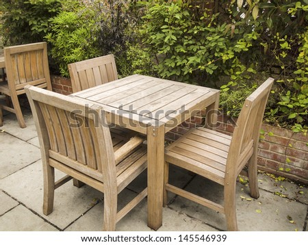 Photo of old wooden table and chairs outdoors with brick barrier and greens trees in background - stock photo