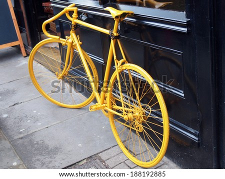 photo of old yellow bike on the window of the coffee shop         - stock photo