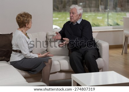 Photo of older married couple discussing at home - stock photo