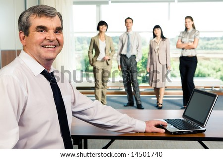 Photo of older smiling leader touching the laptop on the background of working team - stock photo