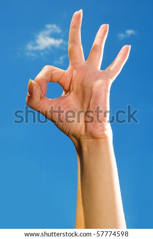 photo of one hand against the blue sky, which shows OK