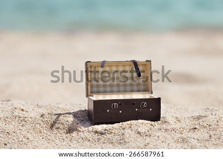 Photo Of Open Miniature Suitcase On Sunny Beach - stock photo