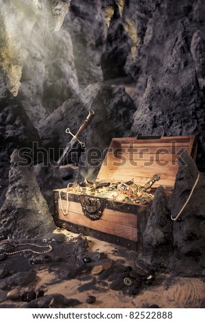 photo of open treasure chest with shinny gold in a cave - stock photo