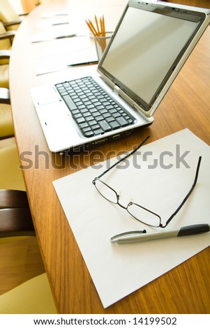 Photo of ordinary objects on the table: glasses and pen over paper with laptop near by - stock photo