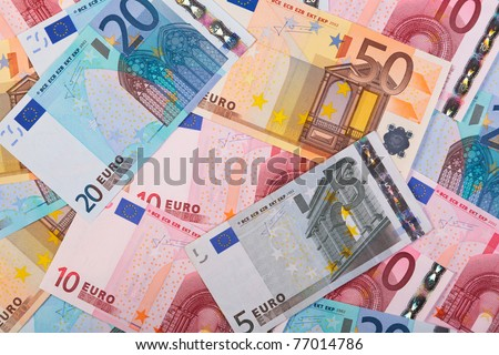 Photo of overlapping Euro banknotes in various denominations.