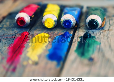 Photo of  4 paint tubes: red, yellow, blue and green - stock photo