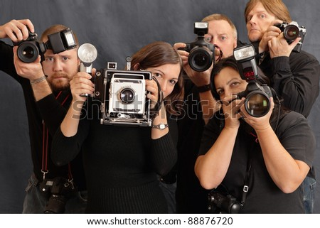Photo of paparazzi waiting for the right moment to take photos. Focus on the two females in front. - stock photo