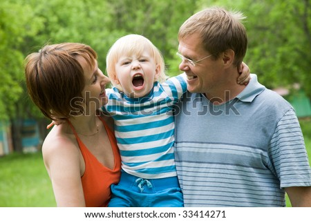 Photo of parents holding son screaming on camera - stock photo