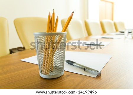 Photo of pencils in plastic glass, some pens and papers on the table in office