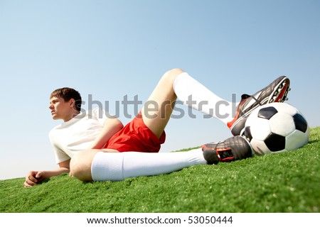 Photo of pensive soccer player lying on green grass-field and resting - stock photo