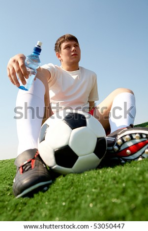Photo of pensive soccer player seated on green grass-field against blue sky