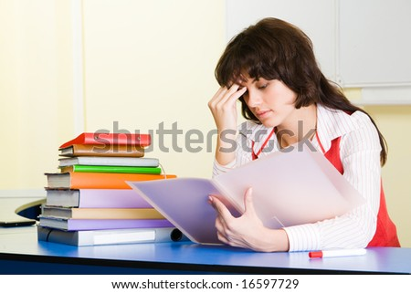 Photo of pensive teacher sitting at the desk and refreshing study material before lesson - stock photo