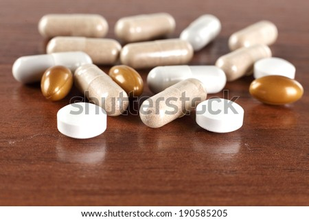 photo of pills and brown decoration of wood