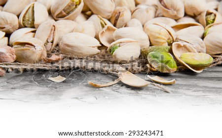 Photo of pistachio nuts on burlap with white space