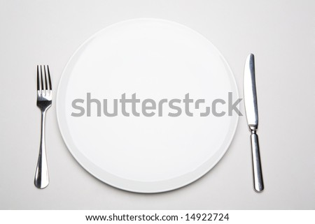 Photo of place in the restaurant: white empty plate with fork and knife near by - stock photo