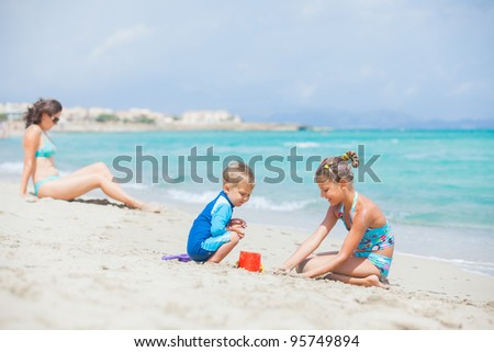Photo of plaing two kids at beach wis his mother - stock photo