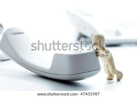 Photo of plasticine white man pushing on telephone receiver - stock photo