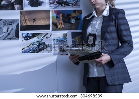 Photo of policewoman with badge and gun presenting crime evidence - stock photo
