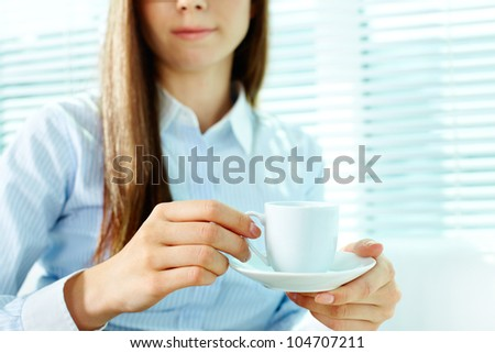 Photo of porcelain coffee cup and saucer in female hands - stock photo