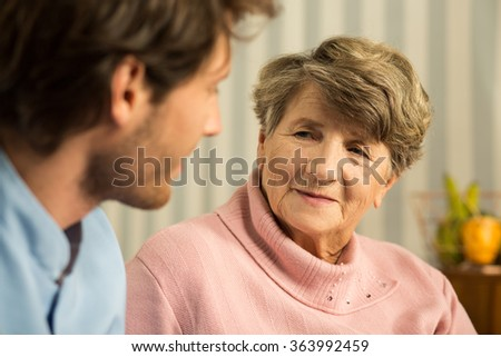 Photo of positive elderly woman with young male carer - stock photo