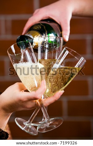Photo of pouring a champagne on the three glasses - stock photo