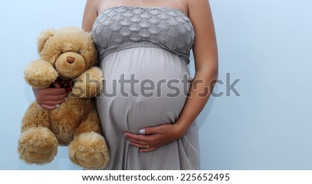 Photo of pregnant woman belly with teddy bear - stock photo