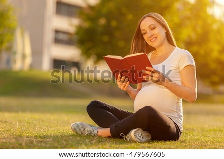 Photo of pregnant woman is reading a book on a green field