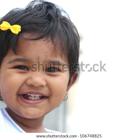 Photo of pretty and happy indian baby girl with expressive eyes and photogenic face expressing toddler's innocence with a beautiful smile. The child is of pre school/kinder-garten age. - stock photo
