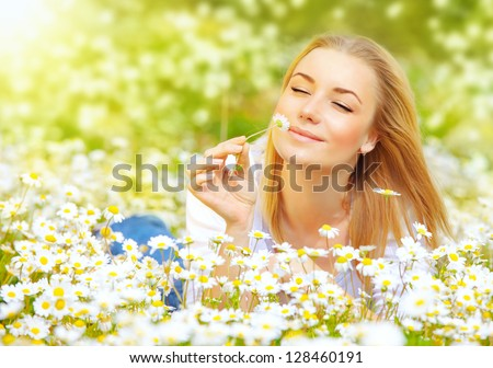 Photo of pretty blonde woman lying down in chamomile field, cute female enjoying smell of daisy, sweet teenager girl with closed eyes relaxed on flowers meadow, spring nature, having fun outdoor - stock photo