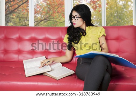 Photo of pretty college student sitting on the sofa while reading textbooks with autumn background on the window