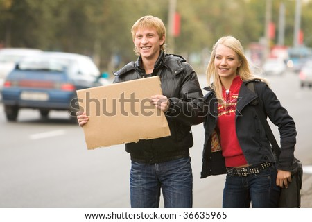 Photo of pretty girl and handsome guy hitchhiking on city road - stock photo