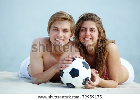 Photo of pretty girl and handsome guy with ball looking at camera on sandy beach - stock photo