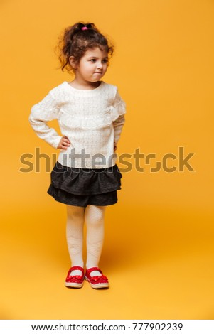 Photo of pretty girl child standing isolated over yellow background. Looking aside.