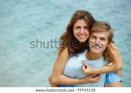 Photo of pretty girl embracing handsome male and both looking at camera - stock photo