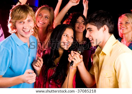 Photo of pretty girl holding microphone while handsome guy speaking or singing in it - stock photo