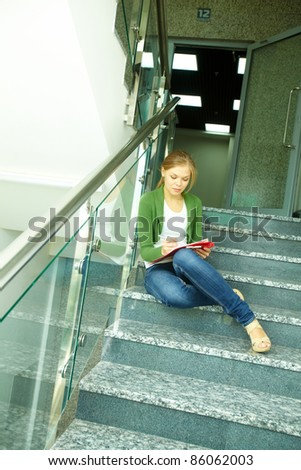Photo of pretty girl sitting on stairs of college and writing something - stock photo