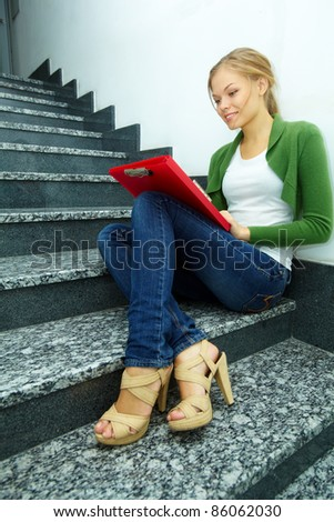 Photo of pretty girl with folder sitting on stairs of college by the wall - stock photo