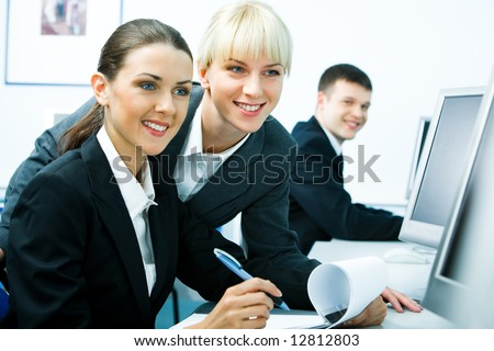 Photo of pretty girls before computer screen looking at it and smiling on the background of young man