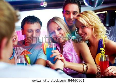 Photo of pretty girls looking at barman with guys near by - stock photo
