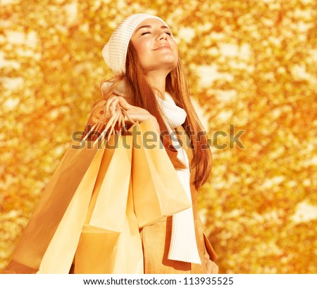 Photo of pretty happy woman with shopping bags in park, smiling cute blond girl enjoying of new purchase over autumn foliage background, fashion and style lifestyle, spending money concept - stock photo