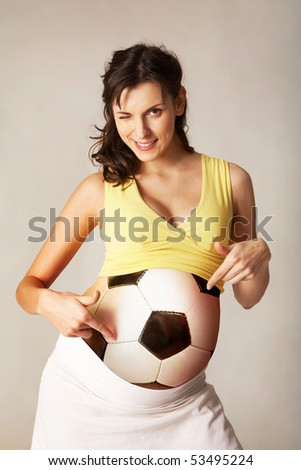 Photo of pretty pregnant woman pointing at her ball belly and winking - stock photo