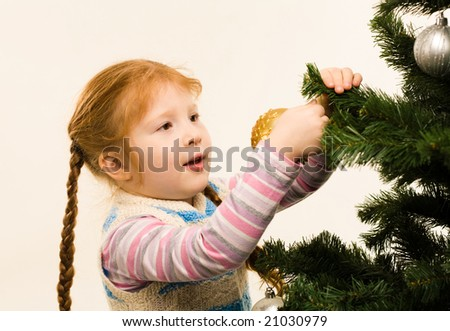 Photo of pretty red-headed girl hanging nice toys on fir tree branches