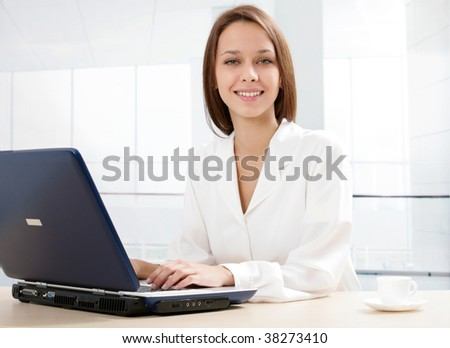 Photo of pretty specialist sitting in office before laptop and looking at camera